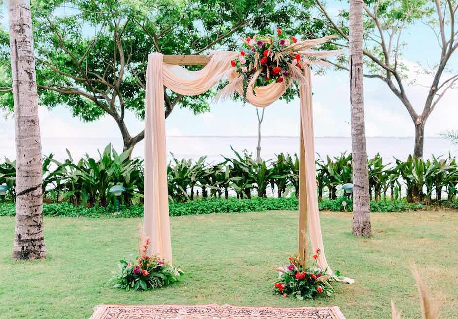 クリムゾン・リゾート&スパ・マクタン<br /> オーシャンフロント・ガーデンウェディング<br /> 挙式会場装飾全景 アーチ