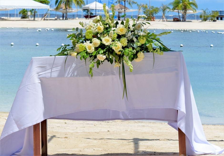 ブルーウォーター・マリバゴ・リゾートビーチウェディングホワイト・ナチュラル祭壇テーブル生花センターピース