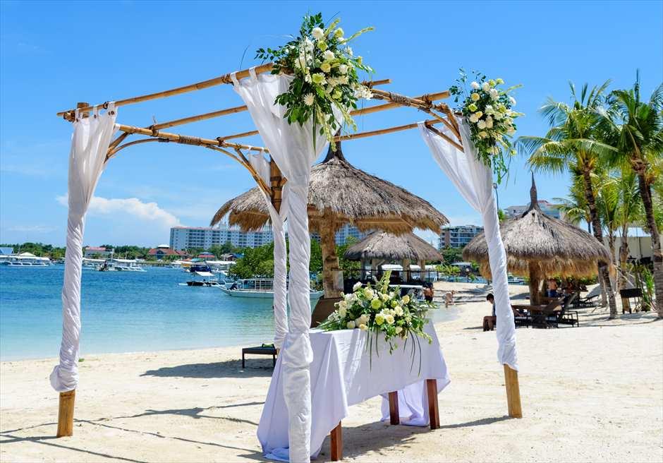 ブルーウォーター・マリバゴ・リゾートビーチウェディングホワイト・ナチュラル祭壇周り生花装飾左舷より望む