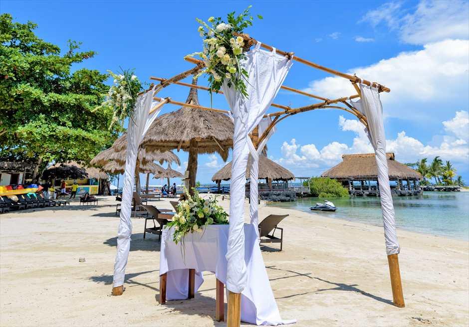 ブルーウォーター・マリバゴ・リゾートビーチウェディングホワイト・ナチュラル祭壇周り生花装飾右舷より望む